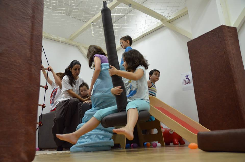 Una terapeuta de NEURAL interactuando con los niños en la sala de rehabilitación infantil (de: http://neural.es/home)