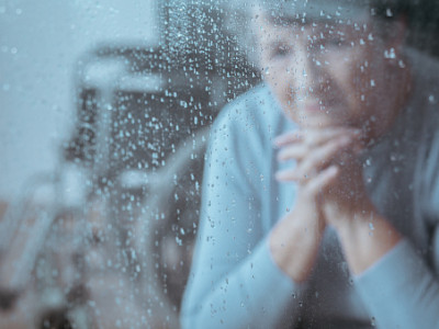 Elder lady with depression sitting alone in the room